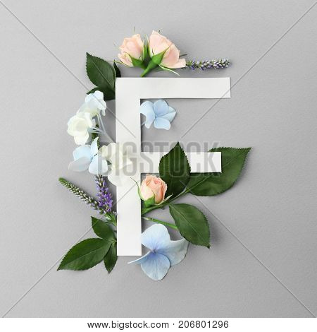 Composition with letter F and beautiful flowers on color background