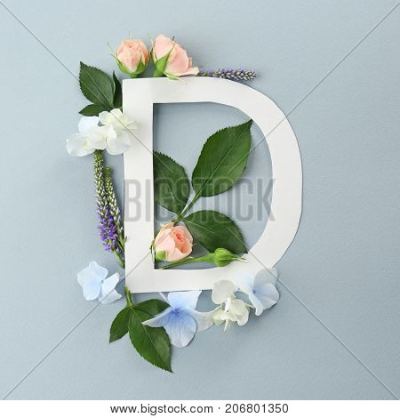 Composition with letter D and beautiful flowers on color background