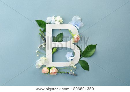 Composition with letter B and beautiful flowers on color background