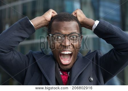 Close Up Portrait Of Desperate Black African American Businessman Screaming In Rage And Anger Tearin
