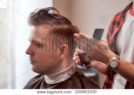 Caucasian young man in Barbershop. Barber is cutting his hair in hipster style. Hair care concept