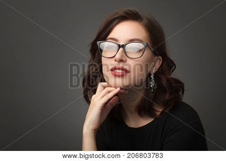 Beautiful brunette woman in black rimmed glasses touching chin looking away wearing black dress posing.