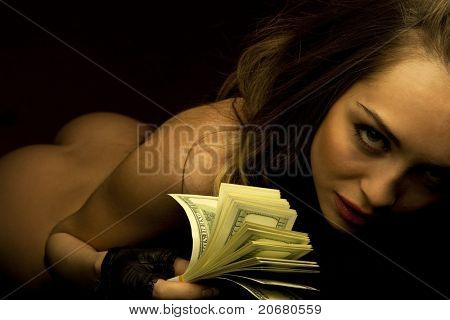 Young sexy female with fan of dollars isolated in darkness