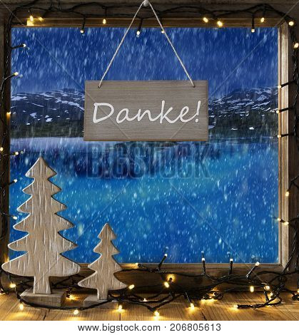 Sign With German Text Danke Means Thank You. Window Frame With Winter Landscape With Snow. View To Snowy Mountains And Lake Or River Outside With Snowflakes. Christmas Tree And Fairy Lights.