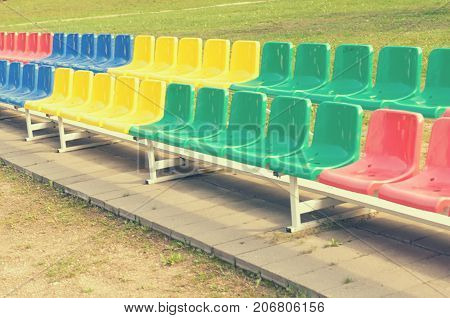 Multicolored benches for sports fans standing in two rows
