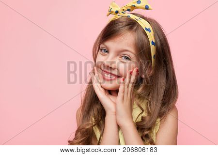 Little adorable girl posing coquettishly in bright headband looking at camera on pink background.