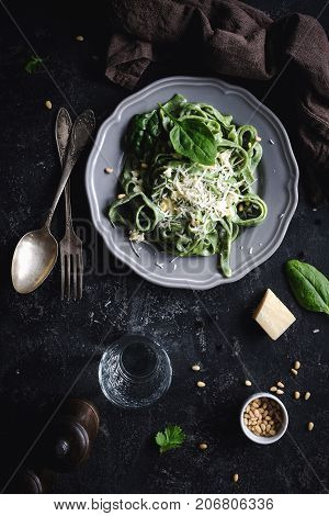 Green spinach pasta with cheese and pine nuts. Top view, dark food photo. Vertical. Homemade healthy green pasta