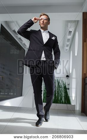 Handsome modern man in stylish suit walking at touching glasses.