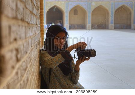 Fars Province Shiraz Iran - 19 april 2017: Young woman on holiday taking a photo with her camera in Vakil Mosque.