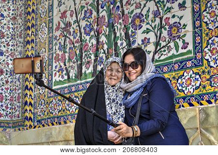 Fars Province Shiraz Iran - 19 april 2017: Two Muslim women dressed in hijabs photograph themselves using a selfie stick and smartphone in the inner courtyard of the Regents mosque.