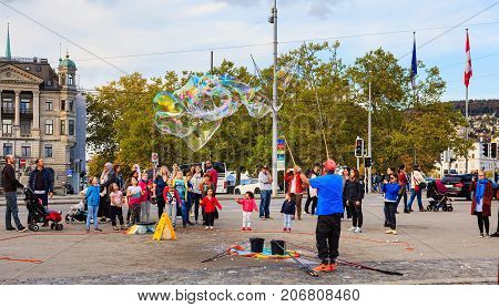 Zurich, Switzerland - 1 October, 2017: people on General Guisan quay watching a street artist making soap bubbles. Zurich lakeside is a popular place among street artist to show their skills.