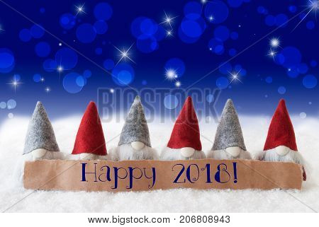 Label With English Text Happy 2018 For Happy New Year. Christmas Greeting Card With Gnomes. Sparkling Bokeh And Blue Background With Snow And Stars.