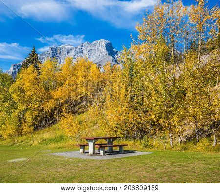 Table and picnic tables in neighborhoods of Lake Minnevanka. Indian Summer in the Rocky Mountains, Canada. The concept of ecological and active tourism
