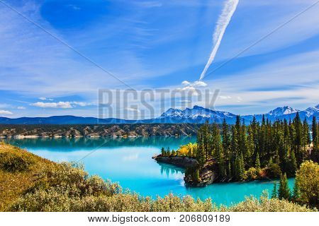 Magnificent turquoise Abraham Lake. Rocky Mountains of Canada in the Indian summer. In the blue sky silver trace of the plane.  The concept of ecological and active tourism