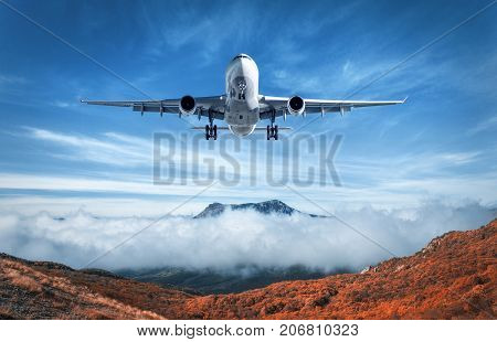 Airplane Is Flying Over Low Clouds And Mountains