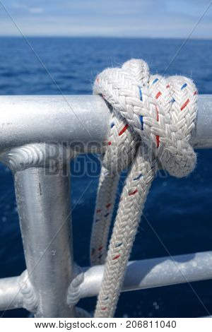 Ship tackle rope with blue and red threads tied to deck railings used for docking at wharf