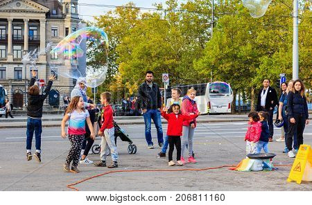 Zurich, Switzerland - 1 October, 2017: people on General Guisan quay watching a street artist making soap bubbles. Zurich lakeside is a popular among street artist place to demonstrate their skills.