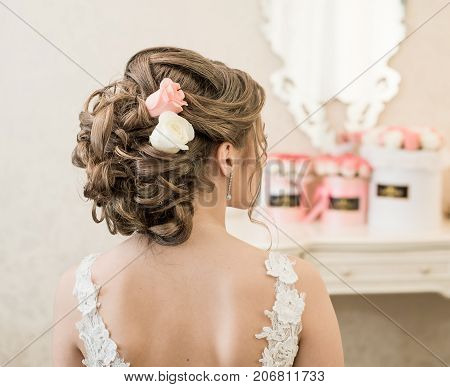 Beautiful bride brunette in white wedding dress with hairstyle and bright makeup. Woman with fashion wedding hair back to camera