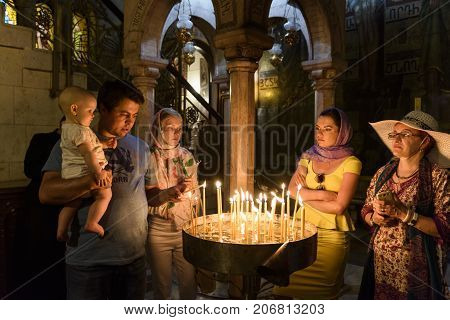 Jerusalem Israel : May 082017Bethlehem Israel May 8 2017: Pilgrims praying with candles into the Saint sepulcre Church in Jerusalem old city