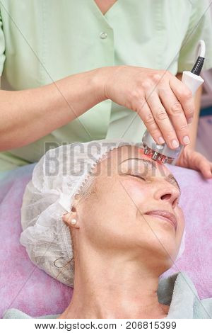 Rf skin tightening, adult woman. Hand of cosmetician working.