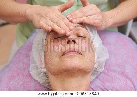 Cosmetician applying facial gel mask. Face of mature woman, cosmetology.