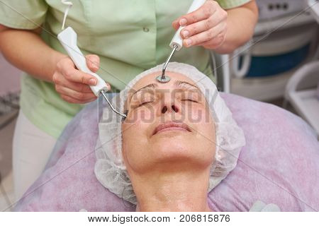 Microcurrent face treatment, adult woman. Work of cosmetician, mature female.