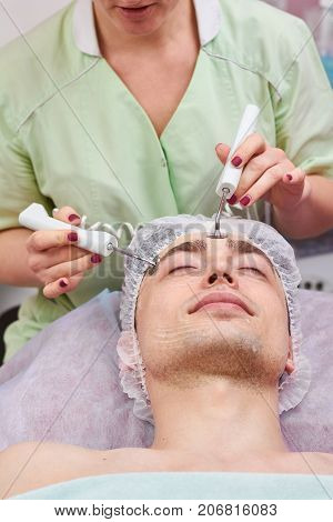 Microcurrent therapy, young man. Cosmetician working with customer.