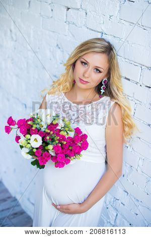 A beautiful pregnant lady with a bouquet of flowers waiting for the baby. Pregnancy. Care, tenderness, maternity, childbirth.