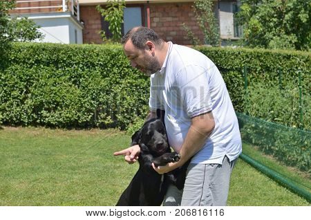 Man cuddling and talking to his best friend - black dog - in a garden
