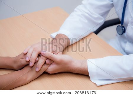 Friendly male doctor hand holding patient hand sitting at the desk for encouragement - empathy - cheering and support while medical examination.