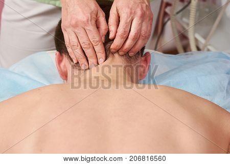 Hands massaging neck close up. Person having neck massage.