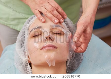 Hands applying collagen facial mask. Face of young woman, cosmetology. Getting rid of acne.