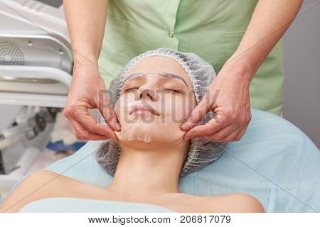 Cosmetician working, collagen mask. Girl in cosmetology clinic.