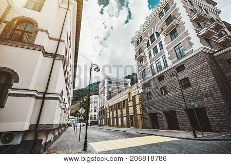 Wide-angle view of completely empty street of small resort district near Sochi city Russia: sunny autumn day sidewalks pillars road pedestrian crossing facades of hotels and inns