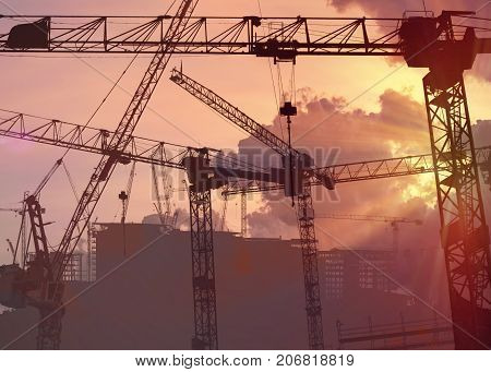 Silhouettes of construction cranes in sunset. Engineering concept.