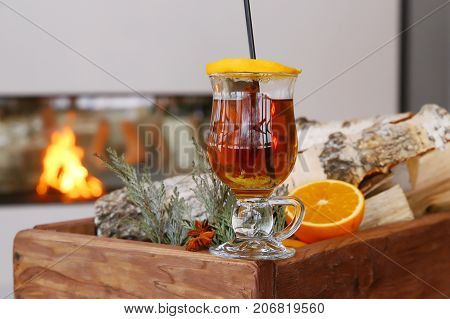 Christmas mulled apple cider with spices cinnamon, cloves, anise and honey on rustic table, traditional drink on winter holiday, magical evening light, selective focus