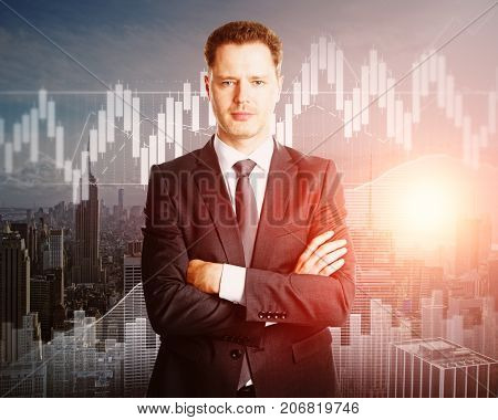 Portrait of handsome young european businessman with folded arms standing on abstract city background with forex diagram. Banking concept. Double exposure