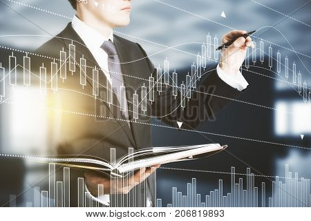 Side view of handsome businessman with document in hands drawing abstract forex chart in blurry interior with sunlight. Trader concept. Double exposure