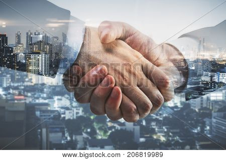 Side view and close up of professional handshake on abstract modern downtown city background. Union concept. Double exposure