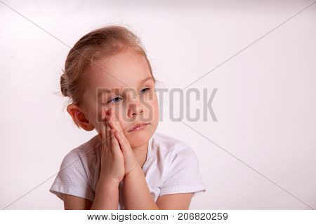 sad child girl folded her hands near the cheek. looking away isolated on white background. sadness. resentment