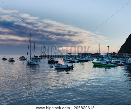 Scenic ocean, island sunrise, bay view of sailboats, yachts, fishing boats in Catalina Island harbor, Avalon, Los Angeles County vacation travel, recreation, tourism, boating destination, peaceful, relaxing, southern California tourist attraction