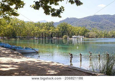 Bañola Lake With Ducks, Boats And A Fishery