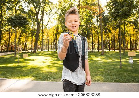 Fashion and beautiful boy with spinner in him hands looking away and playing with fidget toy