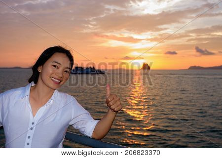 Women raise their thumb to admire the beautiful nature of colorful sky and sun at sunset over the sea on the deck of a passenger boat while cruising to Koh Samui Island in Surat Thani Thailand