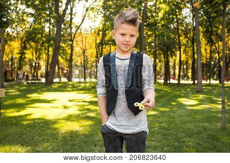 Beautiful and smiling boy in casual wearing with spinner in him hands looking at the camera and playing fidget toys