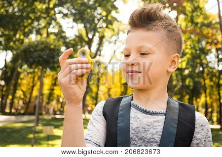 Close up portrait of beautiful boy with yellow spinner and smile. Happy and fun child playing with spinner