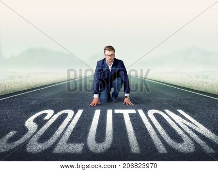 Young determined businessman kneeling before solution text