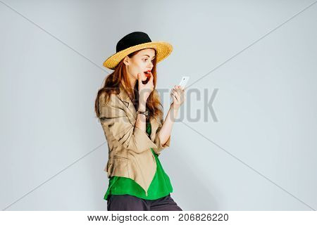 bright girl in a hat looks into her phone and admires