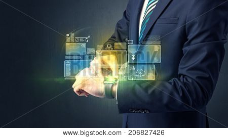 Businessman wearing smartwatch with data symbols and concept.