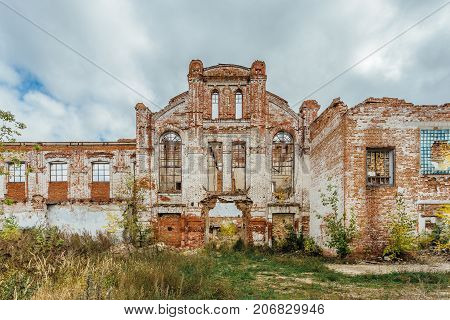 Ruined facade of red brick industrial building in art nouveau style. Abandoned and destroyed sugar factory in Novopokrovka, Tambov region